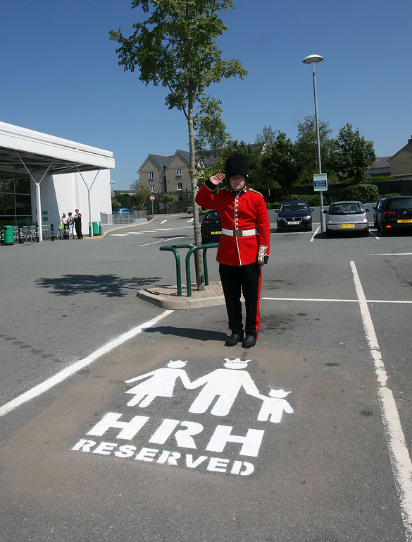 . A man dressed as a member of the queen\'s guard poses beside a parking space reserved for the prospective prince or princess on July 11, 2013, as the Duke and Duchess of Cambridge prepare for the birth of their first child. The supermarket, on the island of Anglesey is situated near to the home that the Duke and Duchess of Cambridge share. (Photo by Richard Birch/Asda via Getty Images)