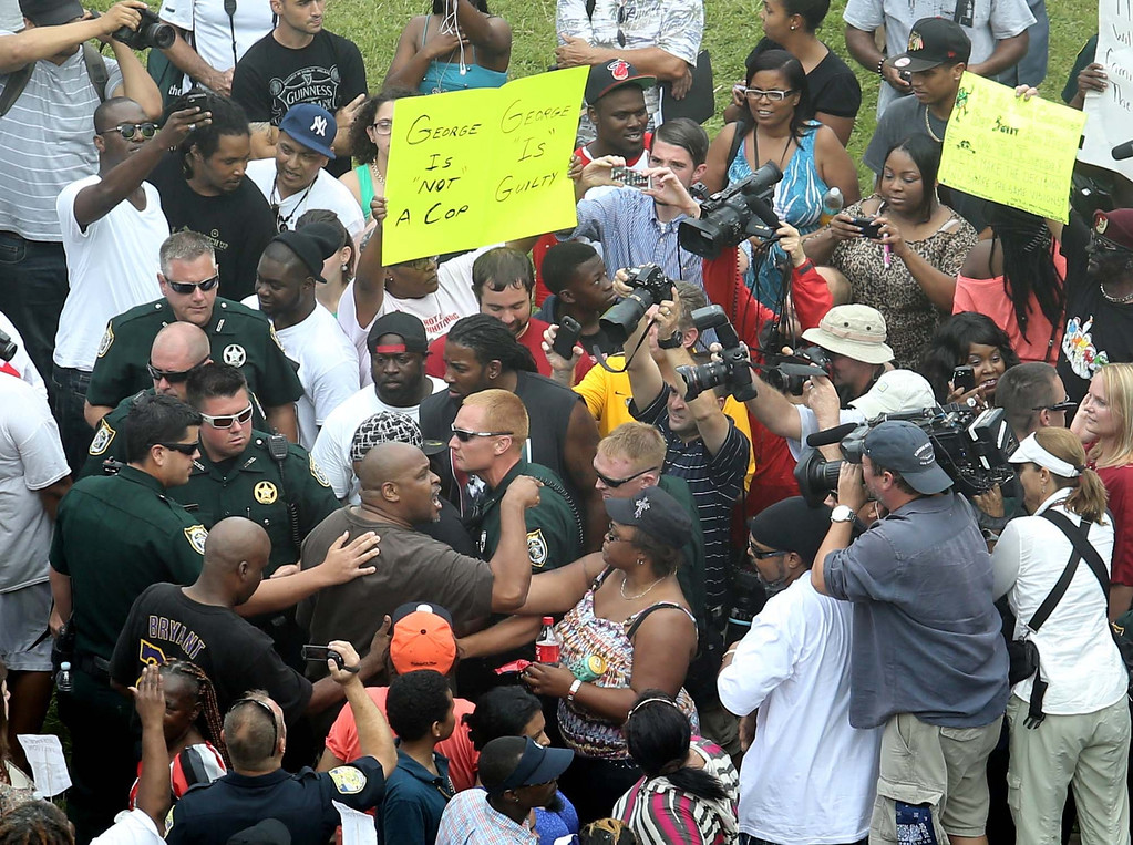 . Deputies try to maintain calm after demonstrators become involved in a shouting match outside the Seminole County Criminal Justice Center during jury deliberations in the trial of George Zimmerman , in Sanford, Fla., Saturday, July  13, 2013. Zimmerman has been charged with the 2012 shooting death of Trayvon Martin.(AP Photo/Orlando Sentinel, Joe Burbank, Pool)