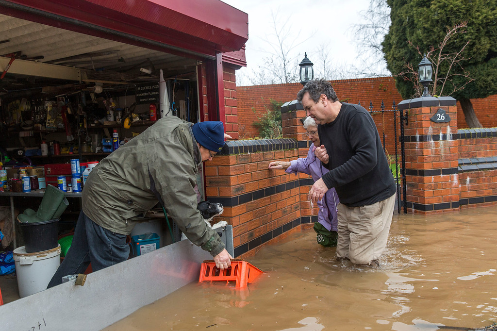 . Dorothy George is helped into her home by sons Andrew George (right) and Laurence George (left) on Waterworks Road on February 12, 2014 in Worcester, England. The Environment Agency has issued flood warnings for dozens of areas along the River Severn. With heavier rains forecast for the coming week people are preparing for for the water levels to rise. (Photo by Rob Stothard/Getty Images)