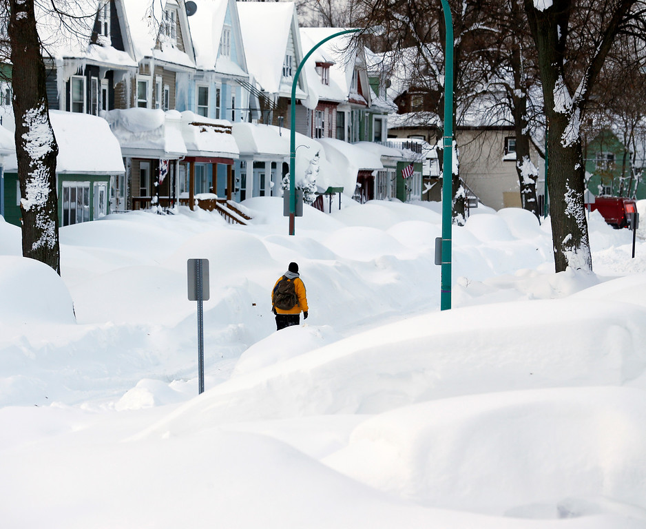 . Brian Cintron walks in his snow-bound south Buffalo neighborhood on Thursday, Nov. 20, 2014, in Buffalo, N.Y. A new blast of lake-effect snow pounded Buffalo for a third day piling more misery on a city already buried by an epic, deadly snowfall that could leave some areas with nearly 8 feet of snow on the ground when it\'s all done. (AP Photo/Mike Groll)