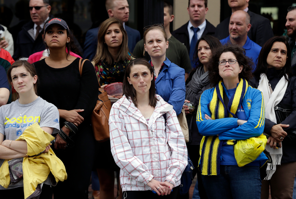 . Heather McDade of Boston, center, reacts while watching a tribute ceremony with others on an over-sized outdoor monitor, Tuesday, April 15, 2014, on Boylston Street in Boston. The ceremony was held for those killed and injured in the bombings at the finish line of the Boston Marathon a year ago. (AP Photo/Steven Senne)