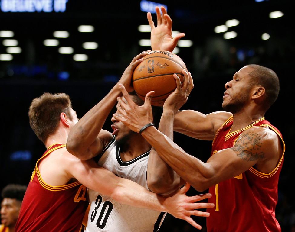 . Cleveland Cavaliers center Timofey Mozgov (20) and Cavaliers guard James Jones (1) surround Brooklyn Nets forward Thaddeus Young (30) in the second half of an NBA basketball game, Wednesday, Jan. 20, 2016, in New York.  The Cavaliers defeated the Nets 91-78. (AP Photo/Kathy Willens)