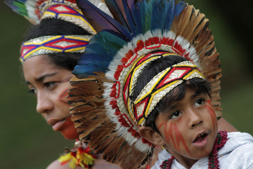 . A Pataxo Indian child with his mother take part in the first day of  the National Indigenous Mobilization protest in Brasilia, Brazil, Tuesday, Oct. 1, 2013.  (AP Photo/Eraldo Peres)