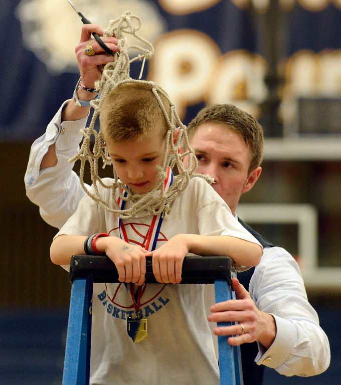 . Maribeth Joeright/MJoeright@News-Herald.com  Villa Angela-St. Joseph coach Babe Kwasniak places the basketball net over his son, Quinn\'s head as they celebrated the team\'s 75-62 victory over Warrensville Height and clinching the Division III district chamionship, March 7, 2014.