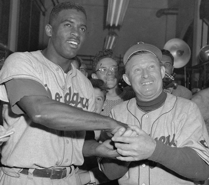 . Brooklyn Dodgers\' Jackie Robinson, left,  is congratulated on his game-winning home run by manager Charley Dressen on  September 30, 1951 in Philadelphia. Robinson broke the color barrier and changed baseball forever. (AP Photo/file)