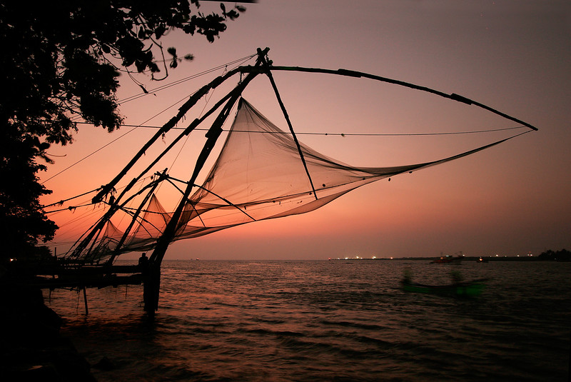 Chinese fishing nets at the fishermen's waterfront by Vasco da Gama Square in Cochin, India. Each giant net is lowered into the water for a few minutes, then hoisted up by a half dozen men. In the early 1500s Vasco da Gama established the European spice trade here.