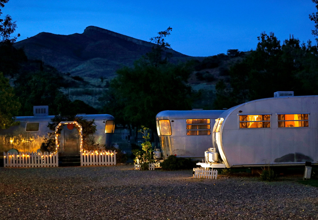 . Windows glow a soft amber hue after dark at the Shady Dell trailer court, Tuesday, April 25, 2017, in Bisbee, Ariz. Founded in 1927 as the as the Thompson Motor Court and later renamed the Shady Dell in the 1950\'s, the rest haven nestled in the tiny copper mining town was a frequent stop for motorists during the golden age of American automobile travel and is a now an off-the-beaten-path destination for travelers and is located 10 miles from the Mexican border. (AP Photo/Matt York)