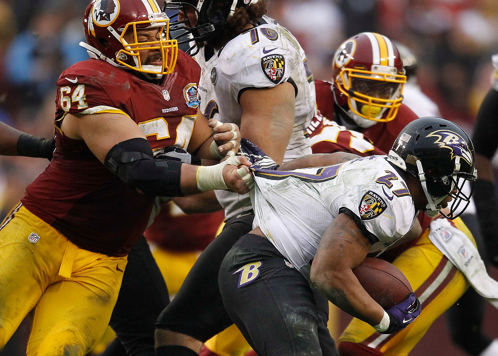 Description of . Washington Redskins defensive lineman Kedric Golston (L) grabs the jersey of Baltimore Ravens running back Ray Rice (R) in the second half of their NFL football game in Landover, Maryland December 9, 2012.     REUTERS/Gary Cameron   (UNITED STATES - Tags: SPORT FOOTBALL)