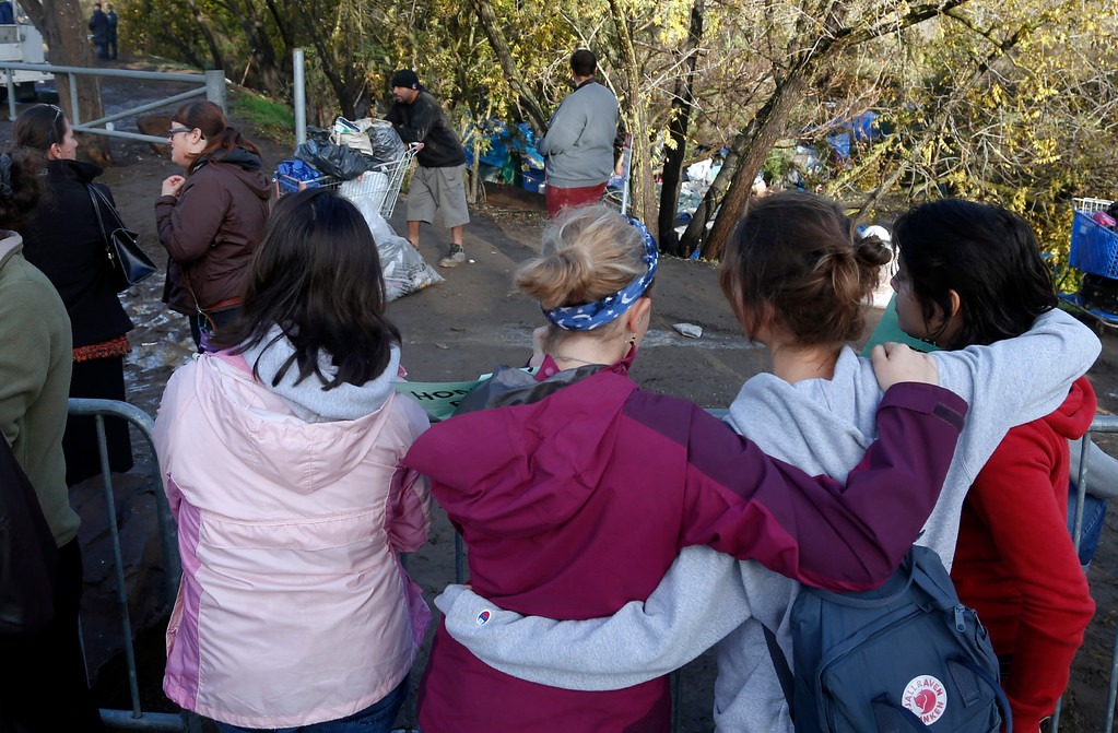 . A group of Stanford University undergraduates watch as residents of The Jungle leave the closed homeless camp on Story Road, Thursday morning, Dec. 4, 2014, in San Jose, Calif. (Karl Mondon/Bay Area News Group)