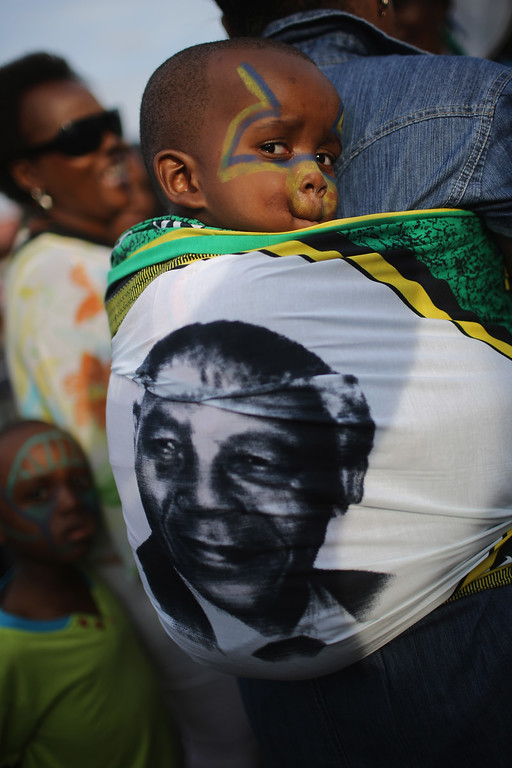 . A young boy sits in a baby sling as ANC supporters sing and dance to celebrate the life of Nelson Mandela outside his former home in Viliakazi Street, Soweto Township, on December 7, 2013 in Soweto, South Africa. Mandela, also known as Tata Madiba, passed away on the evening of December 5th at his home in Houghton at the age of 95. Mandela became South Africa\'s first black president after being jailed for decades for his activism against apartheid in a racially-divided South Africa. (Photo by Christopher Furlong/Getty Images)