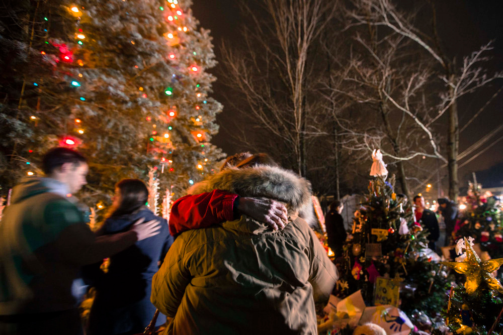 . Mourners embrace while visiting a memorial to the victims of the recent shooting in Sandy Hook Village in Newtown, Connecticut, December 17, 2012. Twelve girls, eight boys and six adult women were killed in a shooting on Friday at Sandy Hook Elementary School in Newtown. REUTERS/Lucas Jackson