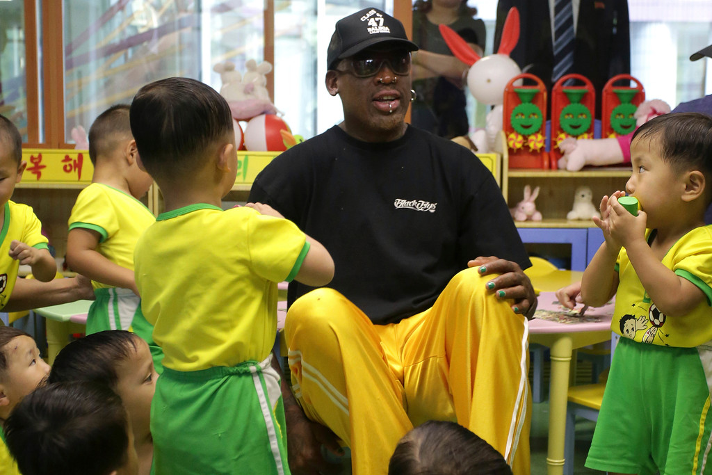 . Former NBA basketball star Dennis Rodman sits with children from the Pyongyang orphanage and nursery that he visited on Thursday, June 15, 2017, in Pyongyang, North Korea. (AP Photo/Kim Kwang Hyon)