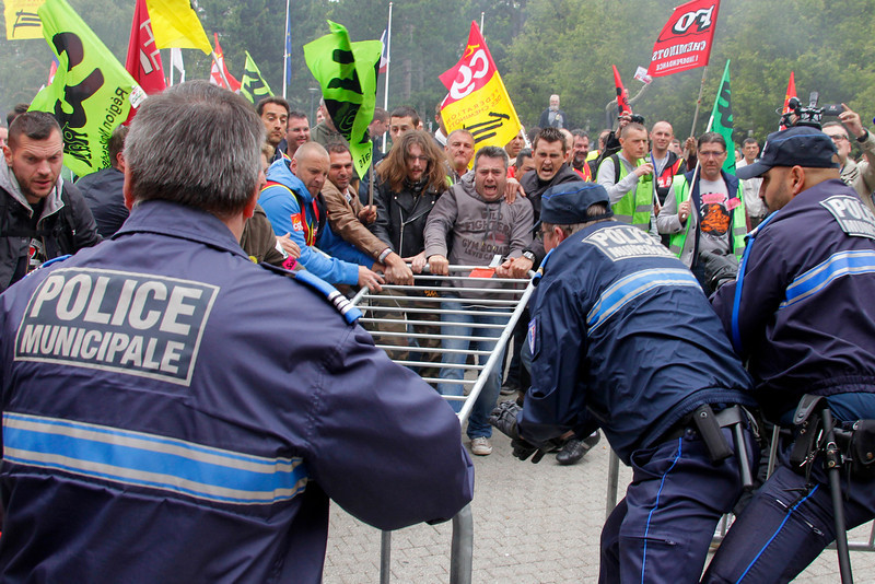 . French rail workers clash against municipal police during a demonstration  in front of the City Hall of Lille, northern France, Tuesday, June 17, 2014. A weeklong strike by French rail workers is heating up as the draft law goes to the lower house of Parliament for debate Tuesday. The bill would unite the SNCF train operator with the RFF railway network, which would pave the way to opening up railways to competition. Workers fear the reform will mean job losses and security concerns. The government says the reform is needed to create a stronger structure for the railways, as France and other European countries gear up for full-scale railway liberalization in coming years.  (AP Photo/Michel Spingler)