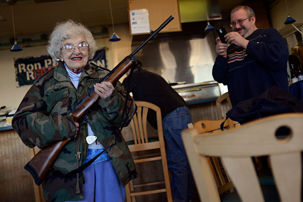 . Lee Lazernick, right, asked his mother Thelma Lazernick, left, to pose with a customer\'s Ruger Mini-14 .223 semi-automatic rifle on Monday, Feb.18, 2013, at All Around Pizza and Deli in Virginia Beach, Va., where customers wearing weapons or who bring their concealed weapons permit are offered at 15 percent discount. (AP Photo/The Virginian-Pilot, Amanda Lucier) MAGS OUT