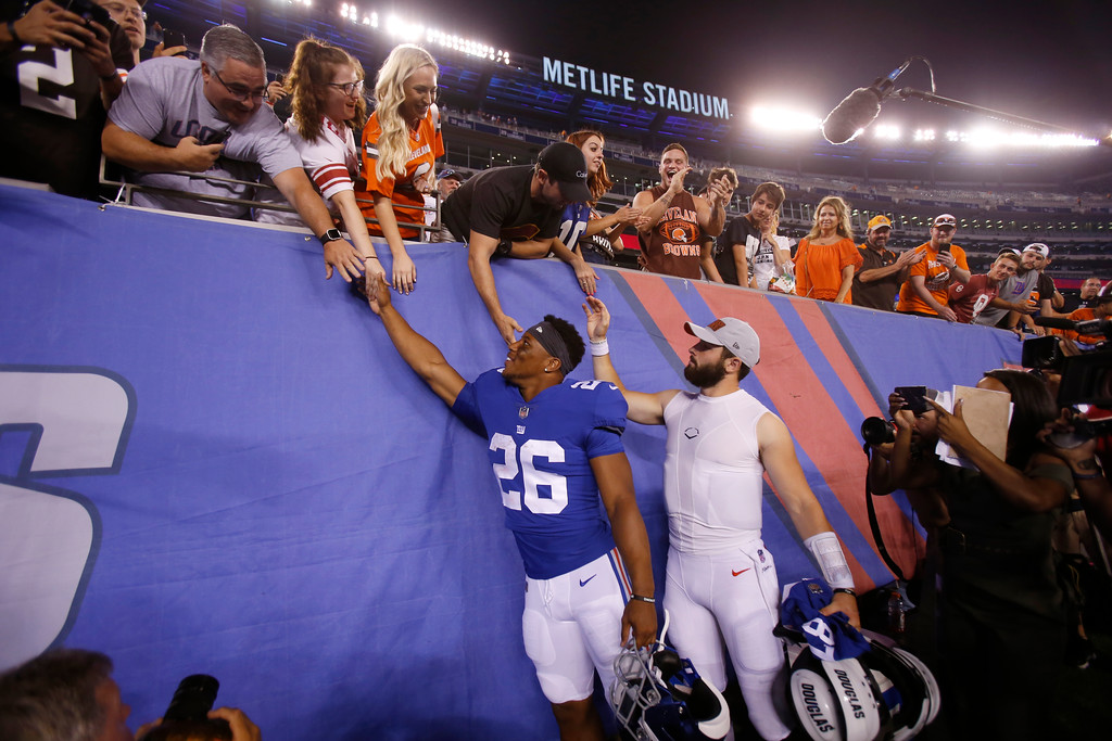 . New York Giants running back Saquon Barkley (26) and Cleveland Browns quarterback Baker Mayfield greet fans after a preseason NFL football game Thursday, Aug. 9, 2018, in East Rutherford, N.J. The Browns won 20-10. (AP Photo/Adam Hunger)