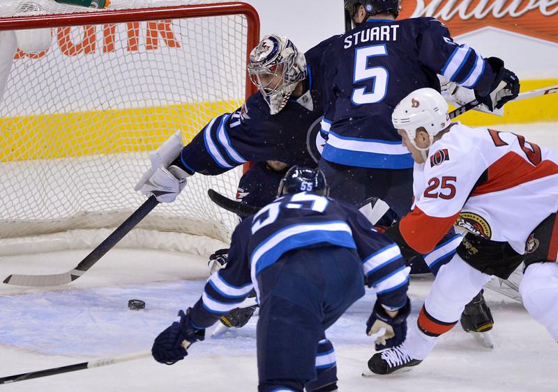 . Ottawa Senators\' Chris Neil (R) scores on Winnipeg Jets goaltender Ondrej Pavelec during the second period of their NHL hockey game in Winnipeg January 19, 2013. REUTERS/Fred Greenslade