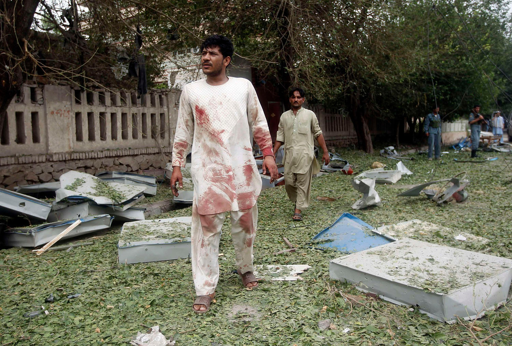 . Men walk at the site of a suicide attack in Jalalabad province August 3, 2013. A suicide bomber attacked the Indian consulate in the eastern Afghan capital of Jalalabad on Saturday, Indian officials and local police said, killing six people and wounding 22. REUTERS/Parwiz