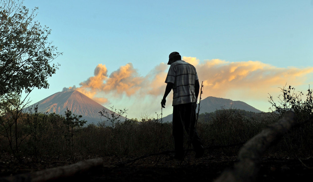 Description of . A man walks in the surroundings of the San Cristobal volcano (background L) in Chonco, Chinandega, 150 km from Managua, on December 26, 2012. The San Cristobal volcano began spewing smoke and ashes on the eve. HECTOR RETAMAL/AFP/Getty Images
