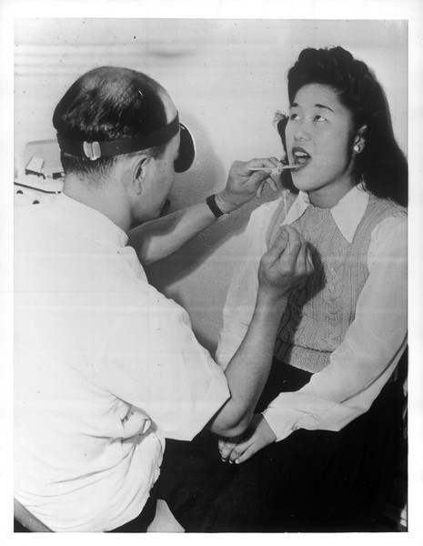 """""""A Japanese doctor examines the throat of a patient at Santa Anita's hospital.""""--caption on photograph"""