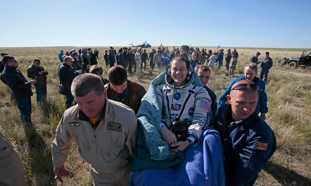 . Ground personnel carry U.S. astronaut Tom Marshburn (C, front) after the Russian Soyuz space capsule landed some 150 km (90 miles) southeast of the town of Zhezkazgan, in central Kazakhstan May 14, 2013.  REUTERS/Mikhail Metzel/Pool