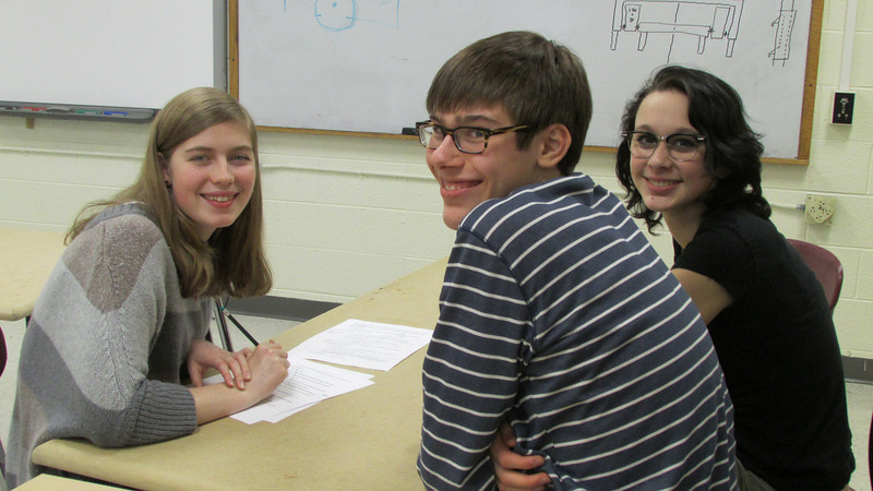 Emma, Grant, and Maya smile while working on Chairmans.