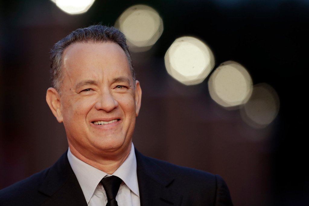 ". FILE - In this Thursday, Oct. 13, 2016 file photo, actor Tom Hanks arrives to receive a lifetime achievement at the Rome Film Festival, in Rome. Within the manic action of ""Inferno,\"" the latest big-screen adaptation of a Dan Brown thriller, is a warning about the dangers of seeking simple solutions to complex problems. Star Tom Hanks says it�s a theme with echoes in the current U.S. presidential race. \""Inferno\"" sets Hank\'s polymathic professor Robert Langdon on the trail of a deadly plague concocted by billionaire scientist Bertrand Zobrist (Ben Foster) out of a sort of warped humanitarianism: He plans to end war, poverty and famine by wiping out half the world\'s population. (AP Photo/Andrew Medichini, file)"