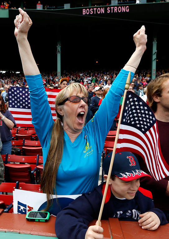 . A fan cheers during a tribute to first responders to the Boston Marathon bombing before a baseball game between the Boston Red Sox and the Kansas City Royals in Boston, Saturday, April 20, 2013. (AP Photo/Michael Dwyer)
