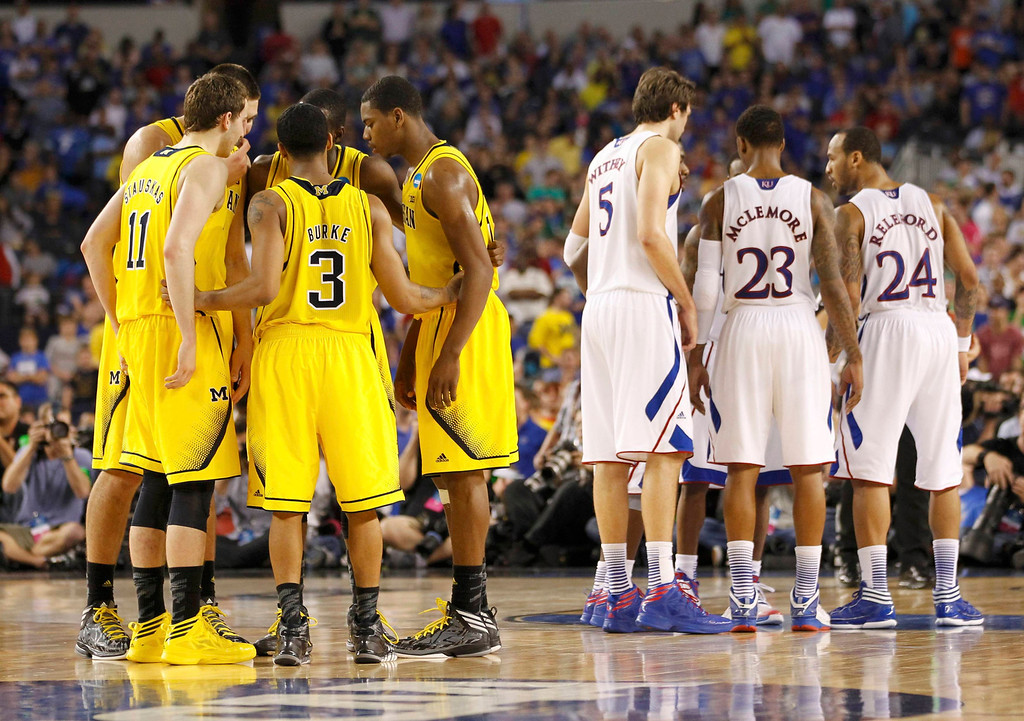 . The Michigan Wolverines and Kansas Jayhawks talk during overtime in their South Regional NCAA men\'s basketball game in Arlington, Texas March 29, 2013. REUTERS/Mike Stone
