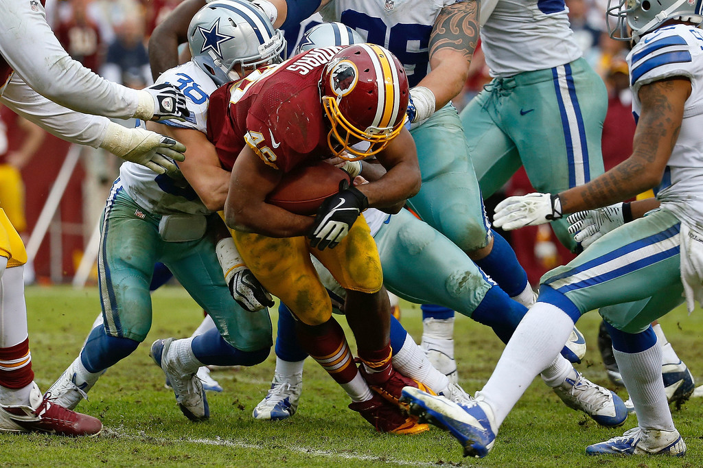 . Washington Redskins running back Alfred Morris is stopped by Dallas Cowboys strong safety Jeff Heath short of the goal line during the second half of an NFL football game in Landover, Md., Sunday, Dec. 22, 2013. Morris scored on the next play. (AP Photo/Alex Brandon)