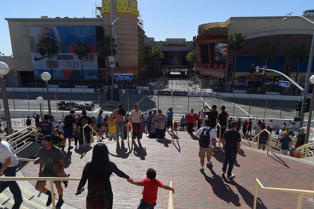 . Fans head down the convention center steps as the Indy cars race up Pine Avenue in Long Beach, CA on Friday, April 17, 2015. The 40th annual Toyota Grand Prix of Long Beach kicked off with practices for all of the racing divisions. (Photo by Scott Varley, Daily Breeze)