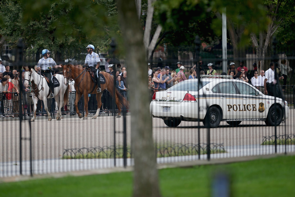 . U.S. Park Police mounted officers and Secret Service Uniformed Division police patrol the perimeter around the White House October 3, 2013 in Washington, DC. The executive mansion was put on lockdown after a report of shots fired at the U.S. Capitol.  (Photo by Chip Somodevilla/Getty Images)