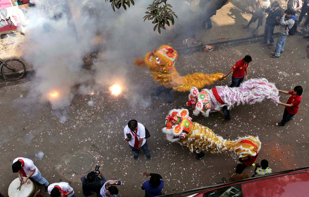 . Chinese lion dance participants of Indian origin perform amid exploding fire crackers on Chinese New Year celebrations in Kolkata, India, Friday, Jan. 31, 2014. The Lunar New Year this year marks the Year of the Horse in the Chinese calendar. (AP Photo/Bikas Das)