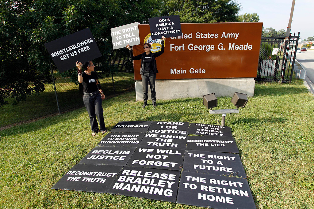 . Supporters of Army Pfc. Bradley Manning hold up signsas they protest outside of the gates at Fort Meade, Md., Wednesday, Aug. 21, 2013, before a sentencing hearing in Manning\'s court martial. The military judge overseeing Manning\'s trial said she will announce on Wednesday his sentence for giving reams of classified information to WikiLeaks.  (AP Photo/Jose Luis Magana)