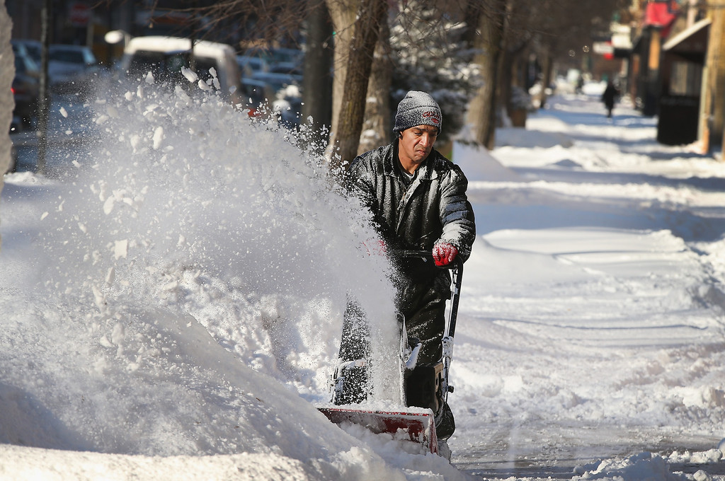 . CHICAGO, IL - JANUARY 21:  Felix Santos clears snow from a sidwalk in the Humboldt Park neighborhood on January 21, 2014 in Chicago, Illinois. A weather system moved through the area overnight dumping from 6 to 12 inches of lake-effect snow on Chicago  and its suburbs while driving temperatures  into the single digits and bringing wind chills as low as 25 degrees-below-zero.  (Photo by Scott Olson/Getty Images)