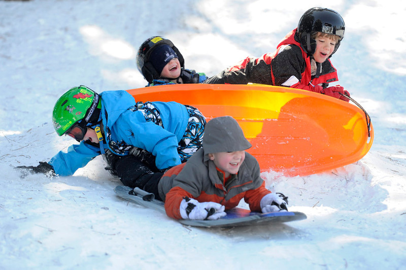 . Clockwise from top Wade Morris, 4, Riley Fleck, 7, Errol Rovinsky, 5, and Devin Morris, 6 vault themselves off a small jump as they and several families gathered at Robinson Park to get in some sledding before the weekend snow begins to melt later in the week with warmer weather forecasted. These Denver families and their kids begin their spring break week today. (Photo By Kathryn Scott Osler/The Denver Post)