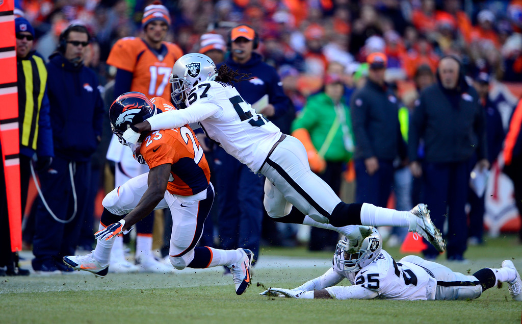 . DENVER, CO - DECEMBER 28: Ronnie Hillman (23) of the Denver Broncos gains three yards as he is taken down by Ray-Ray Armstrong (57) of the Oakland Raiders during the first quarter.  The Denver Broncos played the Oakland Raiders at Sports Authority Field at Mile High in Denver on December, 28 2014. (Photo by Joe Amon/The Denver Post)