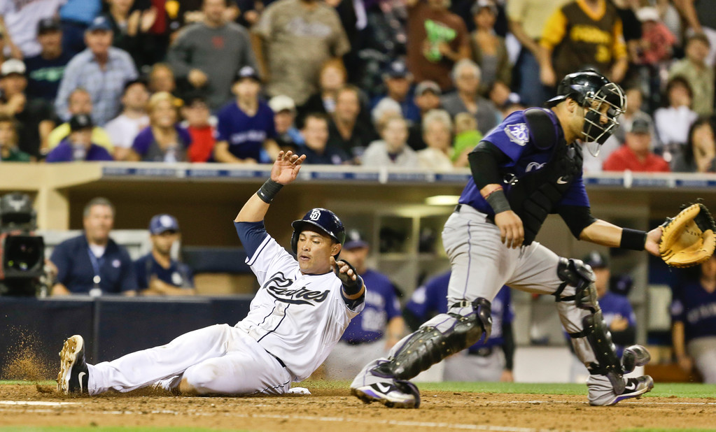 . San Diego Padres\' Everth Cabrera  slides past Colorado Rockies catcher Yorvit Torrealba while scoring on a single by Chris Denorfia in the seventh inning of a baseball game in San Diego, Wednesday, July 10, 2013. (AP Photo/Lenny Ignelzi)