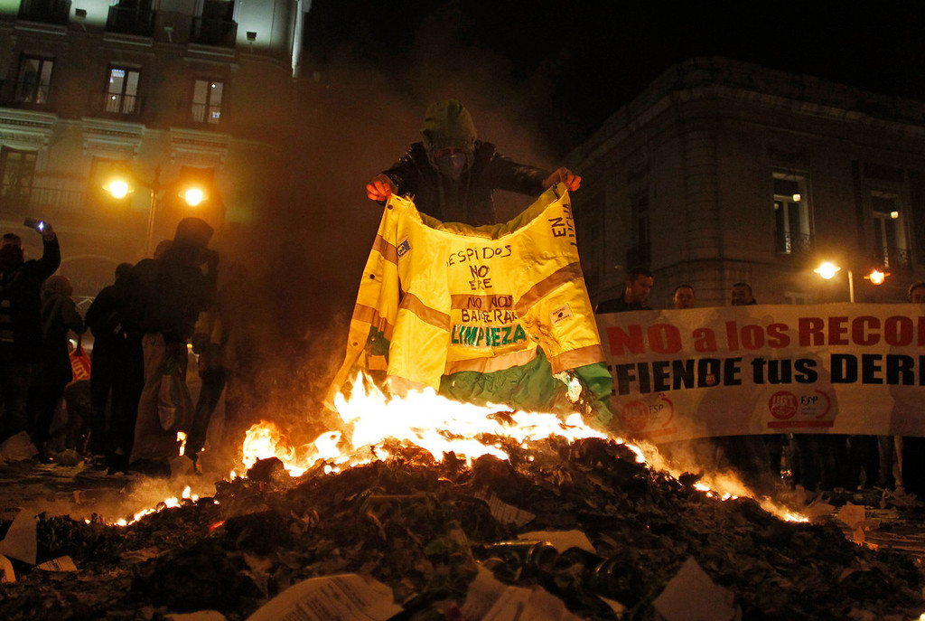 . A protestor burns a street cleaner\'s uniform during a demonstration against layoffs of cleaners and garbage collectors in Madrid, Spain, Monday, Nov. 4, 2013. Trash collectors in Madrid have started bonfires and set off firecrackers during a noisy protest in one of the Spanish capitalís main squares as they prepare to start an open-ended strike. (AP Photo/Francisco Seco)