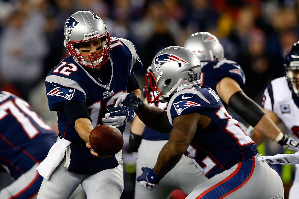 Description of . Tom Brady #12 of the New England Patriots hands the ball off to Stevan Ridley #22 during the 2013 AFC Divisional Playoffs game at Gillette Stadium on January 13, 2013 in Foxboro, Massachusetts.  (Photo by Jared Wickerham/Getty Images)