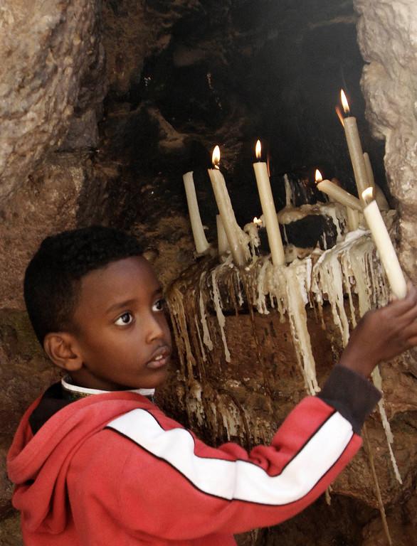 . A Christian boy lights candles during Christmas mass at a Church in Khartoum, Sudan, Wednesday, Dec. 25, 2013. (AP Photo/Abd Raouf)