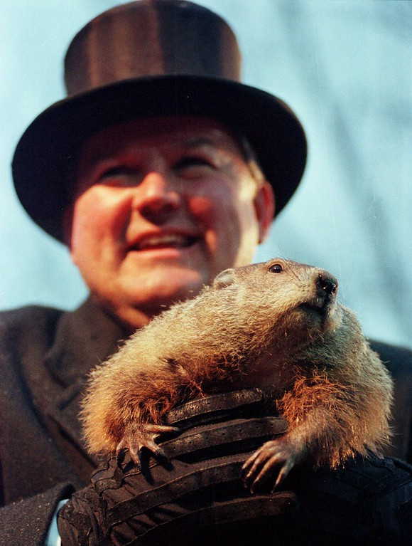 . Punxsutawney Phil is held by handler Bill Deeley after emerging from his burrow Tuesday Feb. 2, 1999 on Gobblers Knob in Punxsutawney, Pa. Phil did not see his shadow and predicted the end of winter weather.(AP Photo/Gene J. Puskar)
