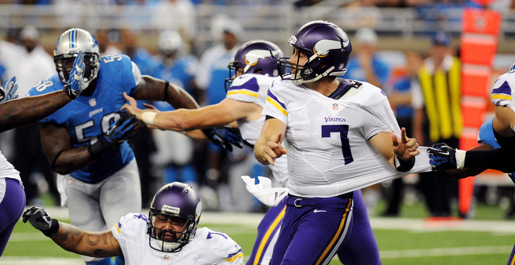 . Vikings quarterback Christian Ponder is in the grasp of a Lions defender as he releases the ball in the second quarter. At lower left is Vikings guard Charlie Johnson.  (Pioneer Press: Chris Polydoroff)
