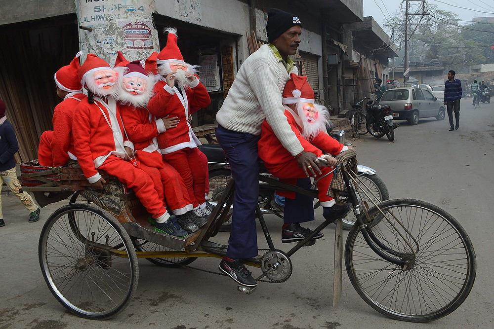 . Indian schoolchildren dressed as Santa Claus ride on a cycle-rickshaw through a street in Amritsar, India on December 24, 2012. Despite Christians forming a little over 2 percent of the billion plus population in India, Christmas is celebrated with much fanfare and zeal throughout the country.  NARINDER NANU/AFP/Getty Images