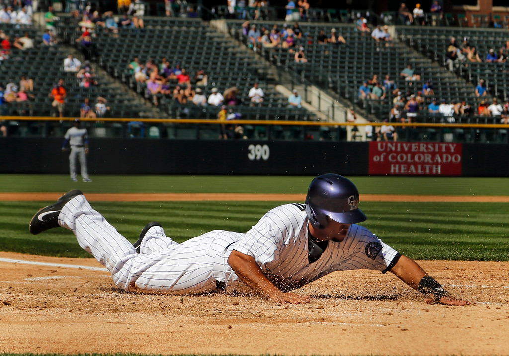 . Colorado Rockies\' Rafael Ynoa slides safely across home plate against the Los Angeles Dodgers during the first inning of a baseball game Wednesday, Sept. 17, 2014, in Denver. (AP Photo/Jack Dempsey)