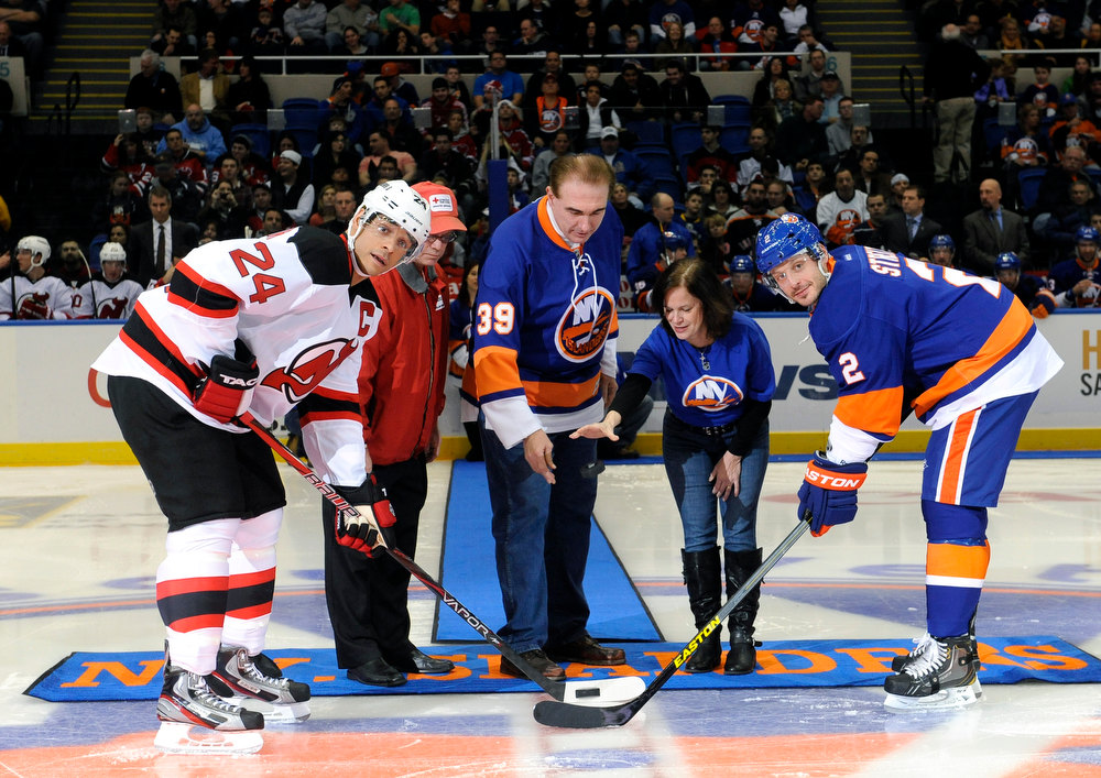 . New Jersey Devils\' Bryce Salvador (24) and New York Islanders\' Mark Streit (2) participate in a ceremonial puck drop by Red Cross Emergency Services Captain Bruce Vesloski, second from left and Tom and Jeanne Gargiulo of Babylon Village, N.Y., whose home was destroyed by Superstorm Sandy, before the start of  an NHL hockey game on Saturday Jan., 19, 2013 at Nassau Coliseum  in Uniondale, N.Y. (AP Photo/Kathy Kmonicek)