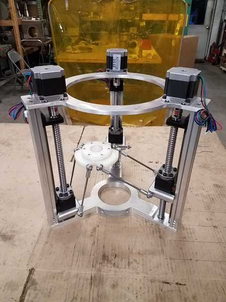 """Delta positioner sits on a 16"""" circular base.  It runs via 3 axes spaced 120 degrees apart.  23 frame steppers and ball screw linear guides are used for the actuators.  These have 8"""" travel."""