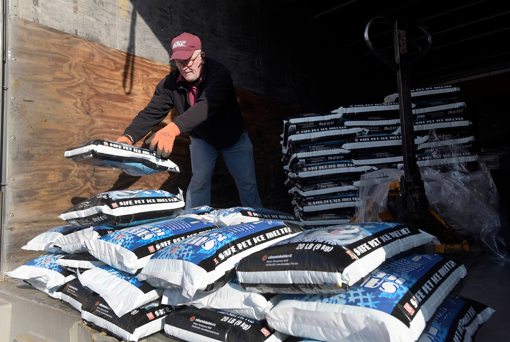 . Truck driver Mike Jock, of Newark, Del., unloads ice-melt in Towson, Md., Thursday, Jan. 21, 2016. The northern mid-Atlantic region, including Baltimore, Washington and Philadelphia, is preparing for a weekend snowstorm that is now forecast to reach blizzard conditions. (AP Photo/Steve Ruark)