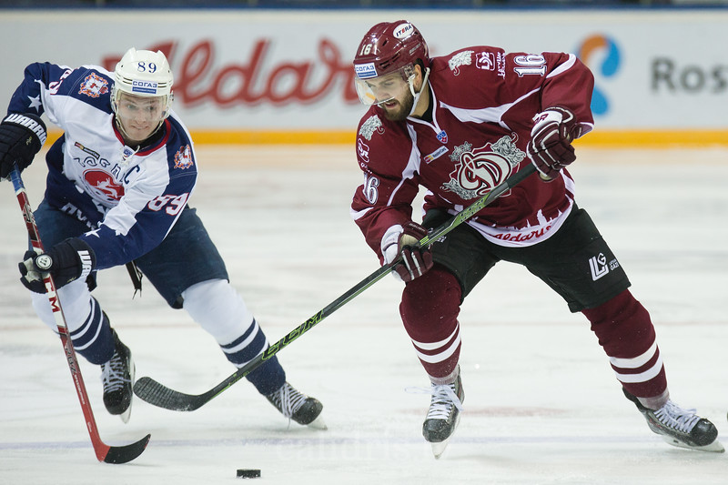 Steven Seigo (16) tries to protect the puck from Alexei Potapov (89) of Torpedo Nizhny Novgorod