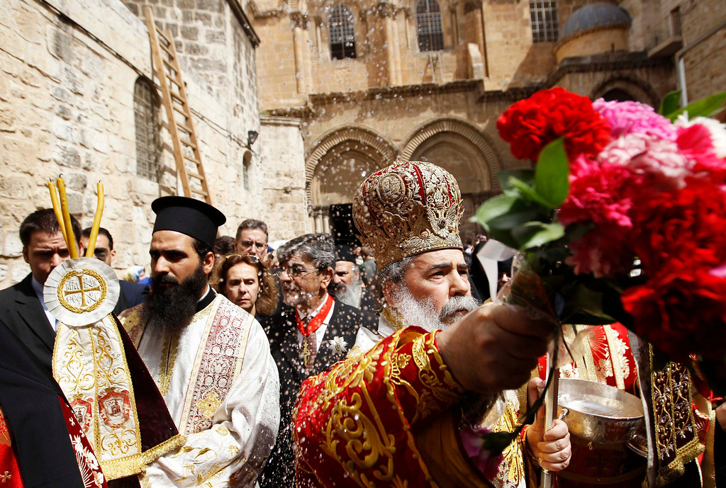 . Greek Orthodox Patriarch of Jerusalem Metropolitan Theophilos (R) blesses the crowd after the washing of the feet ceremony outside the Church of the Holy Sepulchre in Jerusalem\'s Old City May 2, 2013, ahead of Orthodox Easter. REUTERS/Ammar Awad