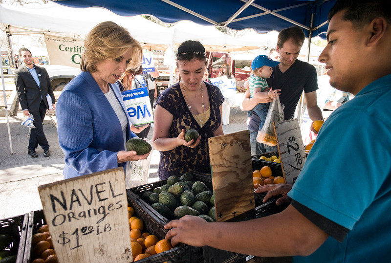 . Wendy Greuel, left, takes a break from her campaign stop at the Encino Farmers Market Sunday to purchase some avocados from Alex Hernandez of Sycamore Hill Ranch.  Greuel is running for Los Angeles mayor.  The election is Tuesday.   Photo by David Crane/Staff Photographer